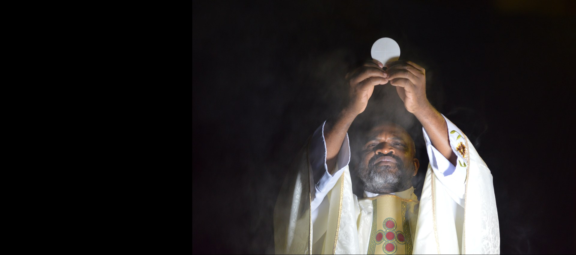 Priest holding up the Holy Eucharist during consecration